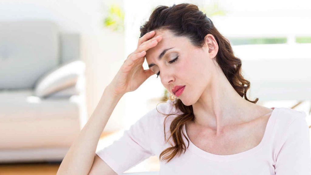 mujer treintona con dolor de cabeza